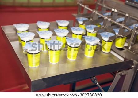 Yogurt filling and sealing machine, automatic packaging machine - stock photo