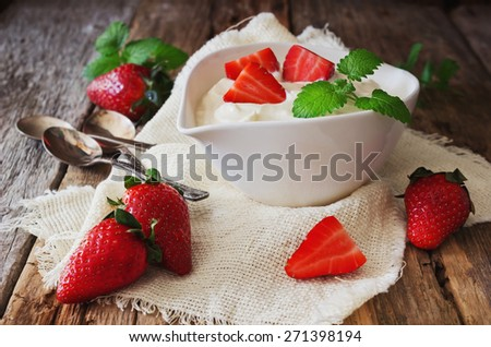 yogurt in a bowl and ripe strawberries on a wooden background. useful dessert.health and diet food. selective focus - stock photo