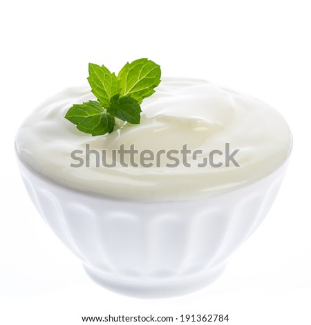 Yogurt in a bowl with a mint leaf - stock photo