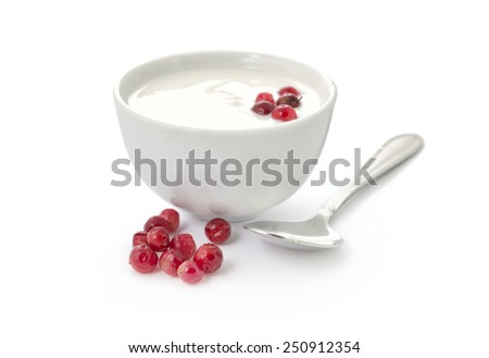 Yogurt in a bowl with cranberries and spoon isolated on white background