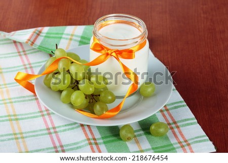 yogurt in a glass jar and fresh green grapes - stock photo