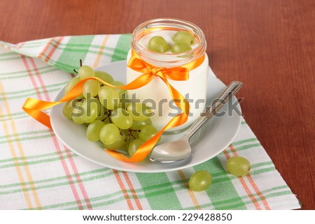 yogurt in a glass jar with spoon and fresh green grapes on wooden background - stock photo
