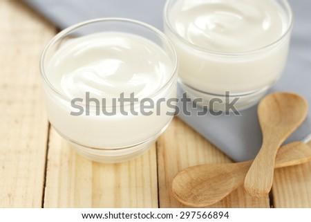 yogurt in glass cup on wooden background with grey cotton and wooden spoon. plain yoghurt. yogurt. yoghurt. - stock photo