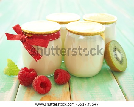 Yogurt in glass jars with fruits - raspberry and kiwi