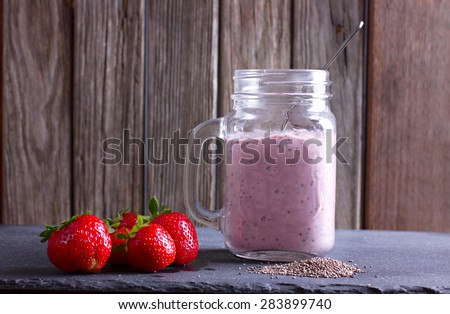 Yogurt in jar with chia seeds and strawberry, fresh strawberries on table - stock photo