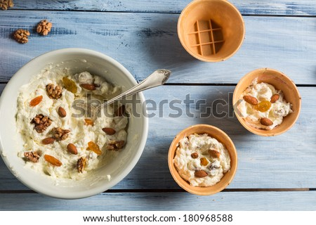 Yogurt mixed with nuts, almonds and raisins as ice cream - stock photo