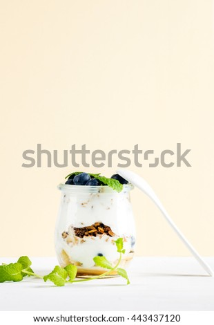 Yogurt oat granola with jam, blueberries and green leaves in glass jar on pastel yellow backdrop, copy space - stock photo