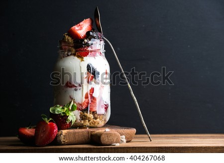 Yogurt oat granola with strawberries, mulberries, honey and mint leaves in tall glass jar on black backdrop, selective focus, copy space - stock photo