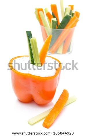 yogurt sauce in half of orange pepper and assorted sliced fresh vegetables in a glass, isolated on a white background