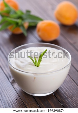 Yogurt with apricots in bowl on wooden background. Selective focus, vertical.