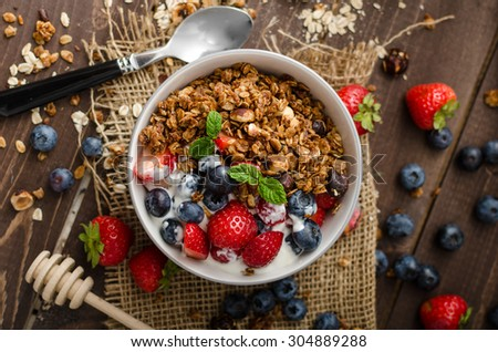 Yogurt with baked granola and berries in small bowl, strawberries, blueberries. Granola baked with nuts and honey for little sweetness. Homemade yogurt - stock photo