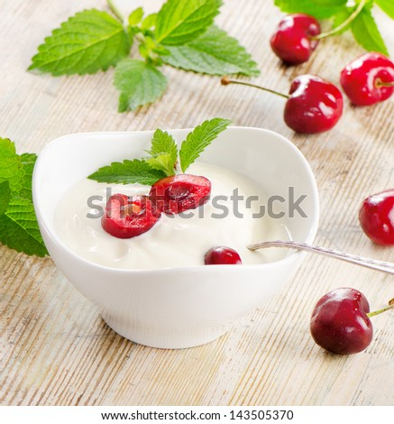Yogurt with berries on a wooden table. Selective focus - stock photo