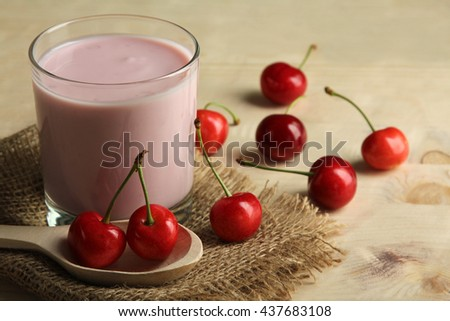 yogurt with cherry flavor in a Cup on burlap on wooden background with wooden spoon - stock photo