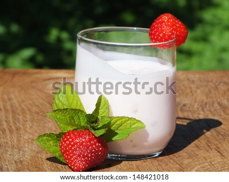 yogurt with fruit on a board made ??of oak wood in the garden - stock photo