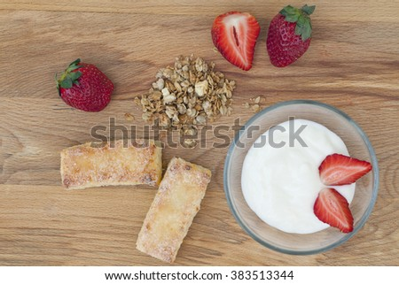 yogurt with muesli and strawberries, a delicious dessert with berries and cookies, healthy Breakfast on wooden background, macro - stock photo