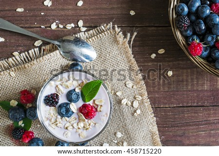 Yogurt with oatmeal or muesli and fresh berries in a glass with a spoon and ripe berries in a wicker bowl. healthy breakfast. top view - stock photo