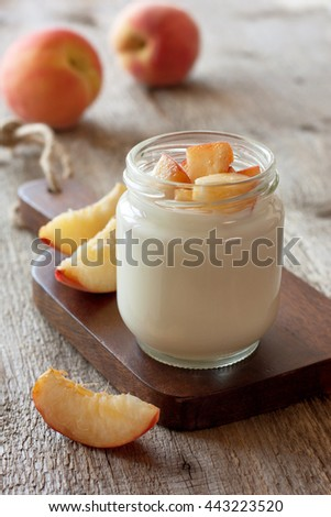Yogurt with peach in a glass jar on the old wooden background. Light diet breakfast - stock photo