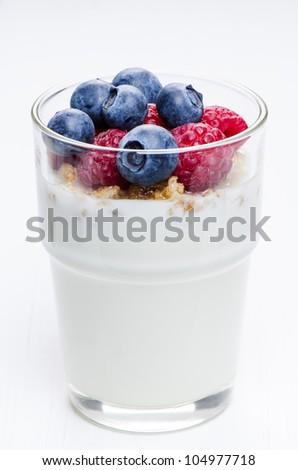 Yogurt with raspberries and blueberries in glass - stock photo