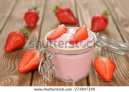 Yogurt with strawberries on a brown background - stock photo