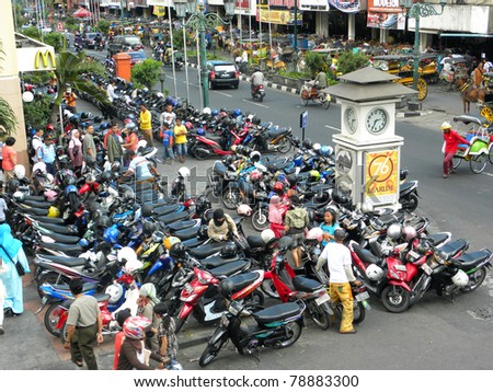 YOGYAKARTA, INDONESIA - JULY 7: View of Yogyakarta with its typical hundreds of motorbikes on July 7, 2009 in Yogyakarta, Indonesia. There is nearly 1 million of motorbikes in the whole city. - stock photo