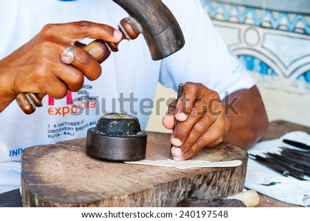 YOGYAKARTA, INDONESIA - SEPTEMBER 15: Man making traditional shadow puppet with leather and hammer in workshop in Yogyakarta, Indonesia on Sept 15, 2014 - stock photo