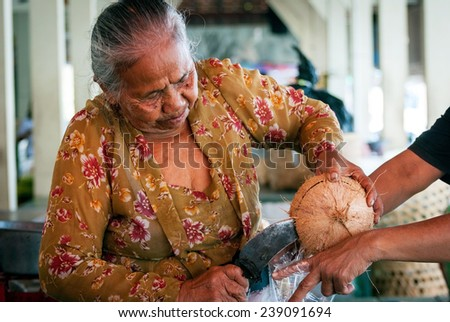 YOGYAKARTA, INDONESIA - SEPTEMBER, 15: Old woman opening coconut to serve coconut milk on the local market in Yogyakarta, Indonesia on Septmber 15, 2014 - stock photo
