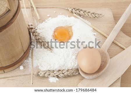 Yolk and egg in flour and spoon on the kitchen table, surrounded by wheat and barrel. - stock photo