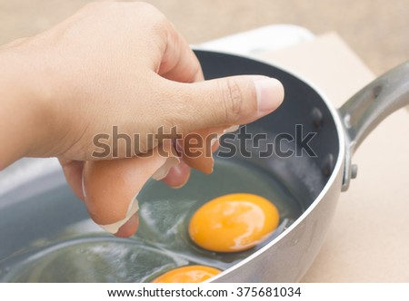 yolk and egg shell of chicken egg in black pan
