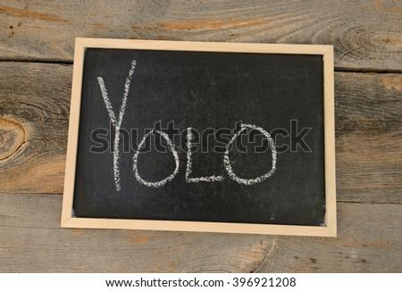 YOLO written in chalk on a chalkboard on a rustic background - stock photo