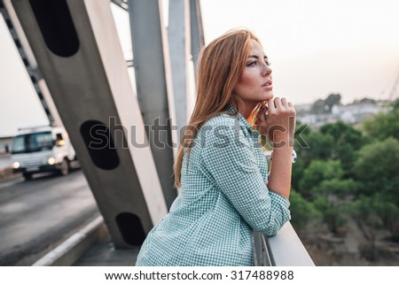 yong adult beautiful woman standing on bridge and looking far away - stock photo