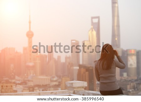 Yong Asian girl looking at the Shanghai sunset