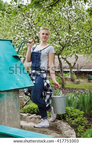 yong blond girl gardener standing with a bucket at the well near country house