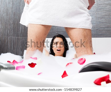 yong couple foreplay lying in jacuzzi, tub red rose petals, concept of intimacy lovers sexy man lover in towel underwear, surprised shocked woman lying looking scared to men's penis genital