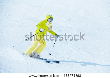 Yong happy skier woman sliding downhill with clean snow white background - stock photo