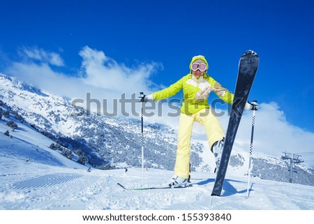 Yong happy woman shows her ski, standing on the mountain slope - stock photo