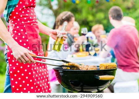 Yong man at the bbq grill turning the meat, in the background friends are having garden party - stock photo