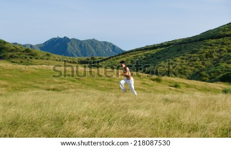 Yong muscular man running on mountain with blue sky - stock photo