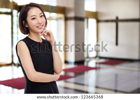 Yong pretty Asian business woman in business background. - stock photo