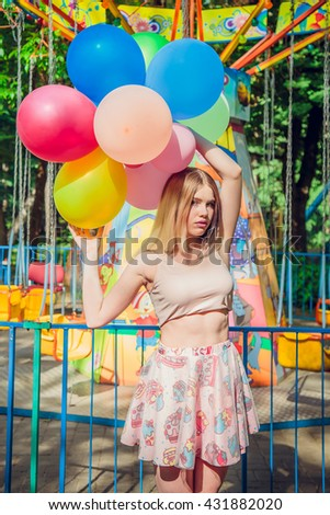 Yong teen girl posing outdoor in summer with colored balloons
