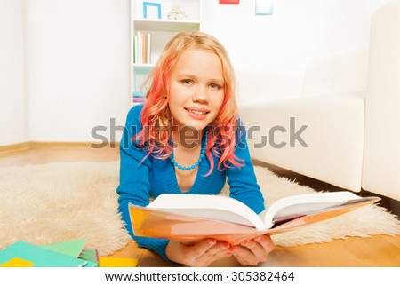 Yong teen girl with pink colored hair laying on the floor in the room reading book - stock photo