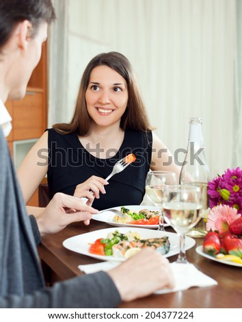 Yong woman having romantic dinner with his husband in home interior - stock photo