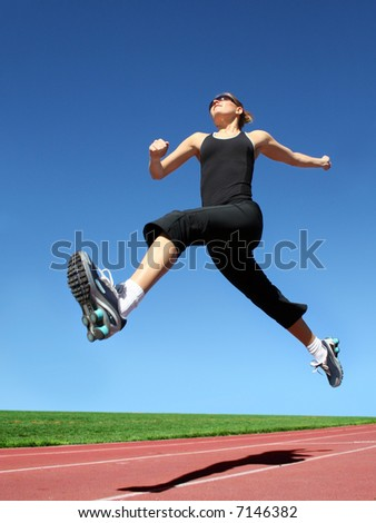 Yong woman running on a racetrack - stock photo