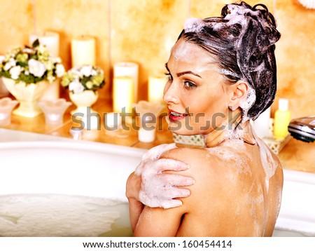 Yong woman washing hair in bubble bath. - stock photo