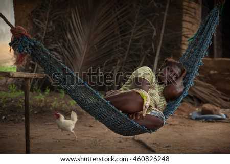 Yongoro, Sierra Leone - June 03, 2013: West Africa, the village of Yongoro in front of Freetown, young woman resting on a hammock in the background passes a chicken