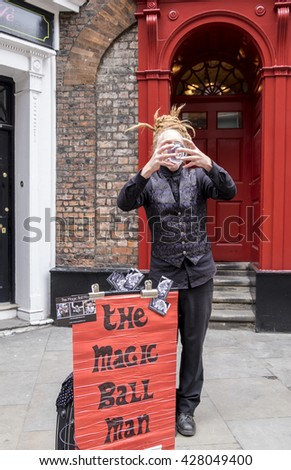 YORK, ENGLAND - 27 MAY 2016 - The Magic Ball Man, an unidentified street performer fascinates passers-by with his tricks using a crystal ball in which you can see his face reflected upside down