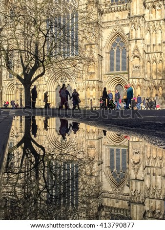YORK, UK - April 30: The Great West Door of York Minster reflected in an 'April Shower' puddle on April 30, 2016 in York.