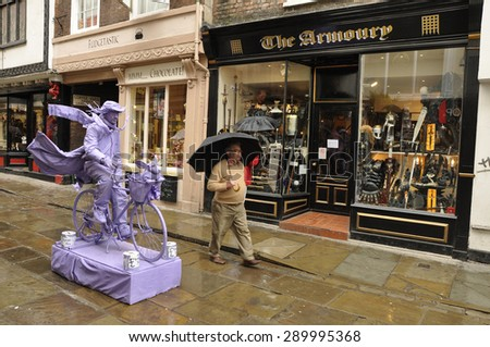 YORK, UNITED KINGDOM - APRIL 19TH: Living statue, a theatrical performance on a rainy day in Stonegate a shopping street in the center of York, North Yorkshire, United Kingdom on April 19th, 2010 - stock photo