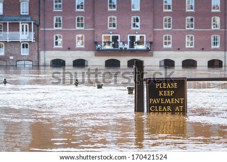 YORK, UNITED KINGDOM - DECEMBER 25, 2013: Flooded pavement in York city center at the bank of the River Ouse, which overflowed due to heavy rains in December 2013. Focus on the sign. - stock photo