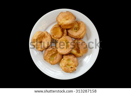 Yorkshire pudding on a white plate, Black Background isolated, From above