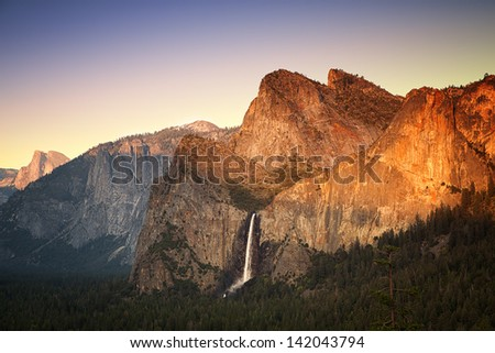 Yosemite at sunset as seen from the Tunnel View viewing point, showing the Half Dome, Cathedral Rocks and the Bridalveil Falls being lit by the setting sun. Yosemite National Park, California, USA - stock photo